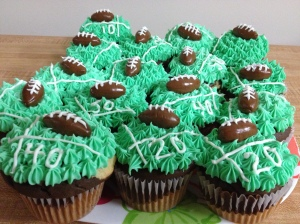 Marble cupcakes with green and white piped icing toped with a Tootsie Roll football.